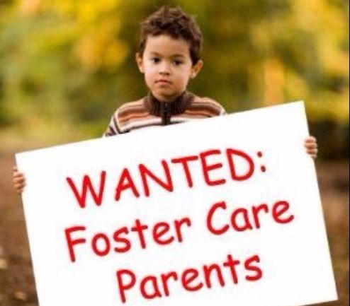 Image shows young boy hold sign that says Foster Parents Needed