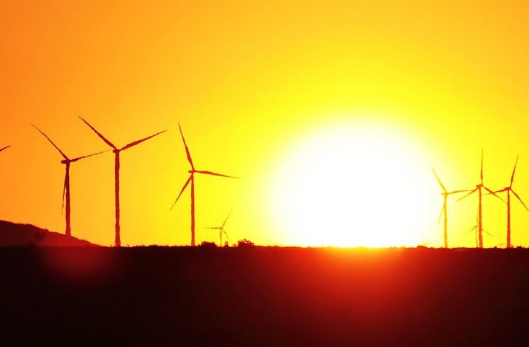 Photo of a Sunset over a landscape with windmills in the background
