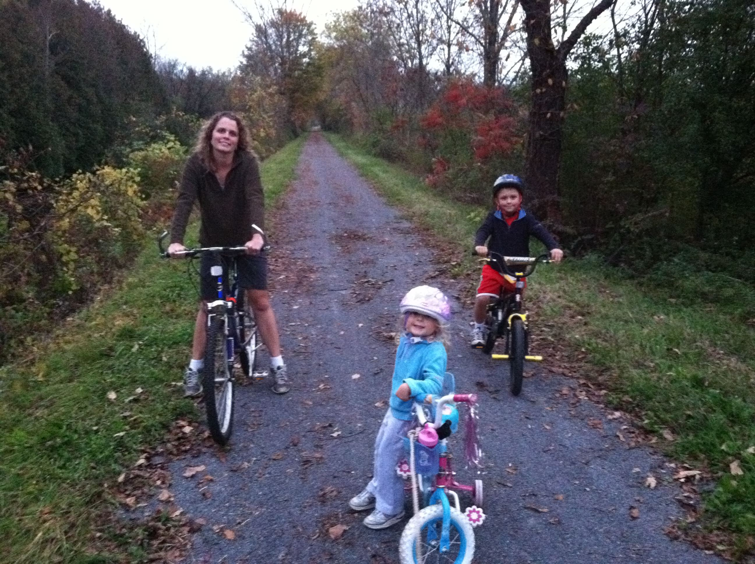 Young family riding bikes on a trail